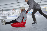 Couple ice skating, using seal sledge to push woman - ZEDF01849