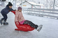 Brother pushing sister on the ice rink,sitting on seal sledge - ZEDF01852