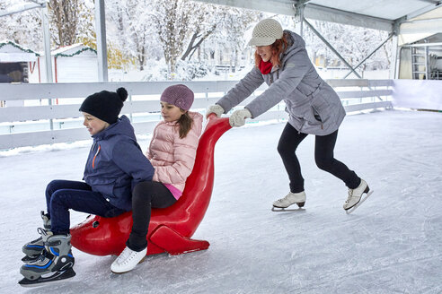 Mother pushing her children on the ice rink, sitting on seal sledge - ZEDF01855