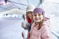 Mother and daughter, drinking hot chocolate on the ice rink - ZEDF01870