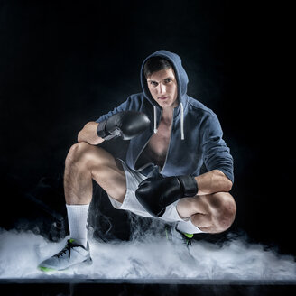 Young boxer against black background with fog - STSF01826