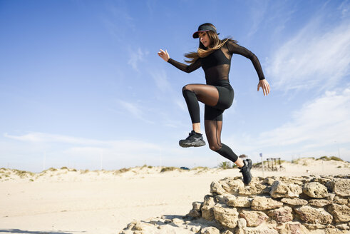 Sportive woman jumping from stone wall on the beach - JSMF00745