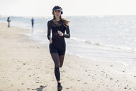 Sportive woman running on the beach - JSMF00751