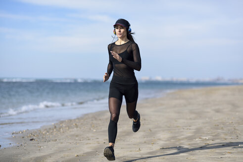 Sportive woman running on the beach - JSMF00754