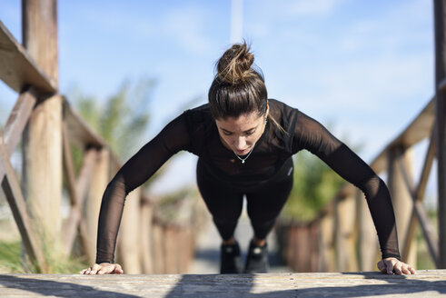 Spain, Andalusia, Cadiz. Middle-aged woman with fit body doing push-ups on a wooden bridge on the beach. Sports and fitness concept. - JSMF00757
