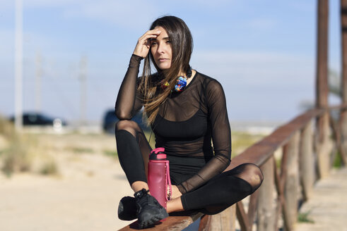 Sportive woman resting after doing sports, sitting on a wooden bridge - JSMF00760