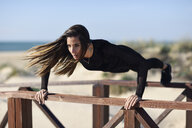 Sportive woman doing push-ups on railing of a wooden bridge - JSMF00763