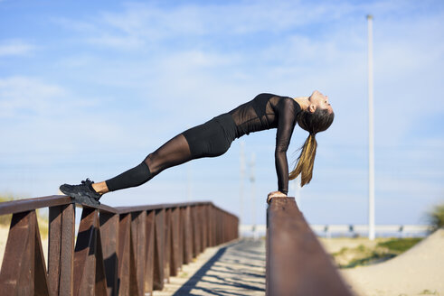 Sportive woman exercising on railing of a wooden bridge - JSMF00766
