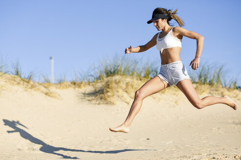 Sportive woman running along sand dunes on the beach - JSMF00769