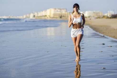 Spain, Andalusia, Cadiz. Middle-aged woman with fit body running barefoot on the beach. Sports and fitness concept. - JSMF00772