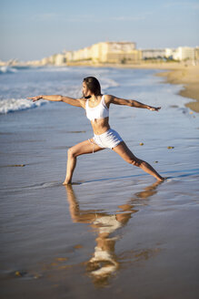 Spain, Andalusia, Cadiz. Middle-aged woman with fit body doing yoga on the beach. Warrior II figure. Sports and fitness concept. - JSMF00775