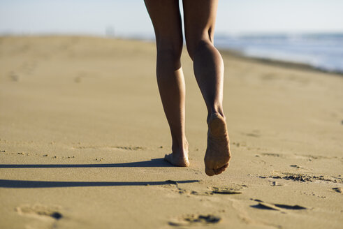 Close-up of woman's legs walking in sand on the beach - JSMF00781