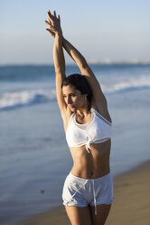 Sportive woman stretching on the beach - JSMF00787