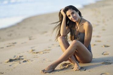 Portrait of beautiful woman wearing swimsuit sitting on the beach - JSMF00790