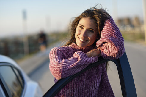 Portrait of smiling woman leaning on car door - JSMF00793