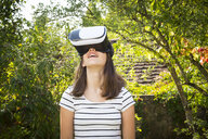 Amazed girl wearing Virtual Reality Glasses in the garden - LVF07714