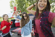 Women cheering at tailgate barbecue in field - HEROF08147