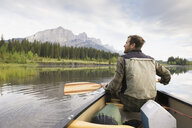Man sitting in canoe in still lake - HEROF08210
