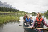 Family sitting in canoe in still lake - HEROF08246