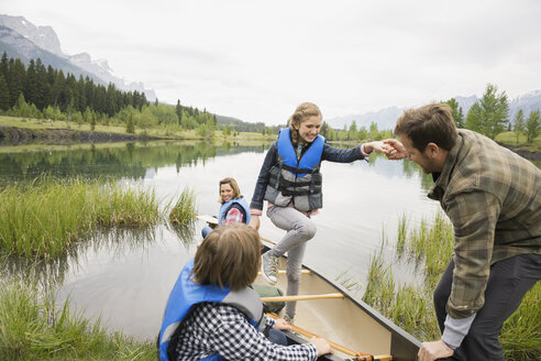Father helping daughter from canoe in still lake - HEROF08258