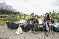 Family sitting by canoe by still lake - HEROF08264
