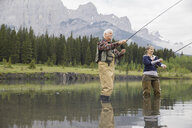Older couple fishing in still lake - HEROF08270
