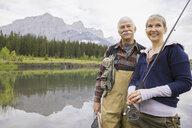 Older couple fishing in still lake - HEROF08273