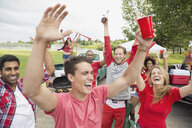 Friends cheering at tailgate barbecue in field - HEROF08312