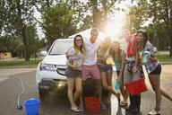 Portrait of friends washing car - HEROF08348