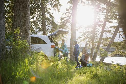 Family unpacking car at campsite - HEROF08363