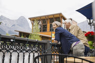 Older couple leaning on banister outdoors - HEROF08378