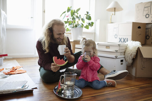 Father and daughter eating watermelon and drinking water, taking a break from moving and painting - HEROF08414