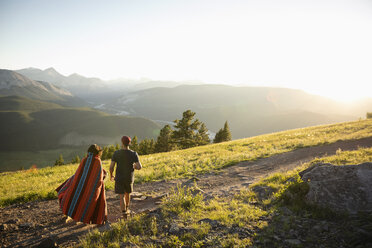 Couple wrapped in blanket walking on sunny mountain hilltop, Alberta, Canada - HEROF08450