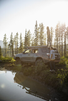 Couple enjoying overland adventure, standing at SUV in sunny remote forest, Alberta, Canada - HEROF08453