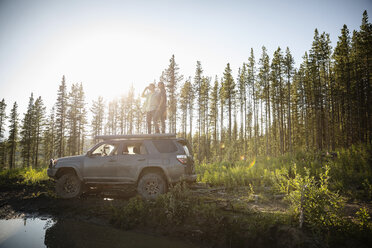 Couple enjoying overland adventure, standing on top of SUV in sunny remote forest, Alberta, Canada - HEROF08456