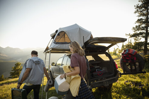Couple camping, unloading SUV with rooftop tent in sunny field, Alberta, Canada - HEROF08459