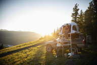 Couple camping, relaxing at SUV rooftop tent in sunny, idyllic field, Alberta, Canada - HEROF08462