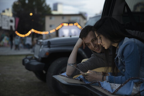 Couple with digital tablet relaxing in back of SUV at night - HEROF08519
