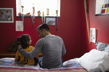Father talking to son in soccer uniform on bed - HEROF08561