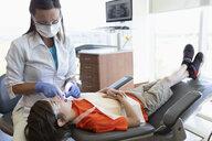 Dental hygienist flossing teeth of boy in dentist office - HEROF08573