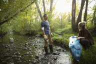 Man and woman volunteering, cleaning up garbage in stream - HEROF08627