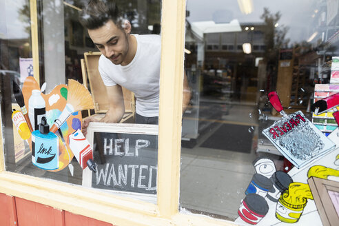 Male business owner placing Help Wanted sign in art supply shop window - HEROF08648