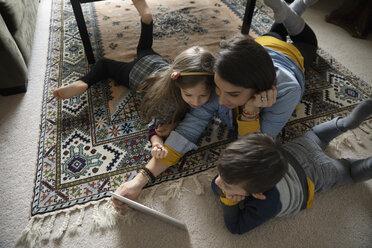 Latinx family using digital tablet on living room floor - HEROF08657