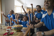 Latinx multi-generation family watching sports and cheering - HEROF08666
