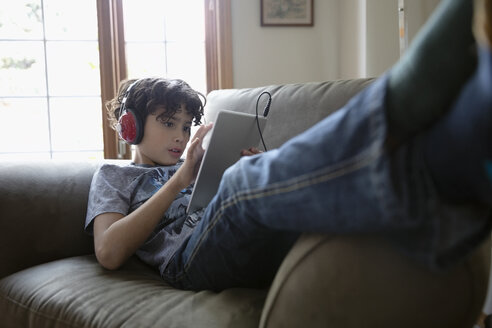 Latinx boy with headphones using digital tablet on sofa - HEROF08669
