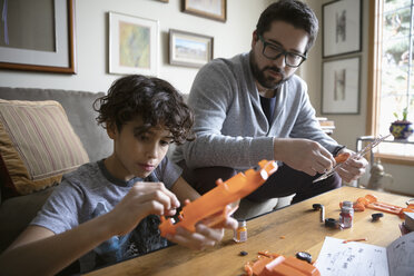Latinx father and son assembling model car - HEROF08675