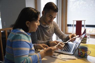 Latinx man helping senior mother paying bills at laptop - HEROF08681