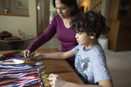 Latinx grandmother and grandson looking at sports medals - HEROF08690