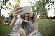 Playful, affectionate teenage girl friends hugging, taking selfie with camera phone in park - HEROF08726