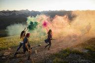 Playful friends enjoying colorful smoke bombs on sunny mountain road, Alberta, Canada - HEROF08747
